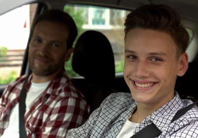 Młody chłopak uczy się jeździć samochodem
