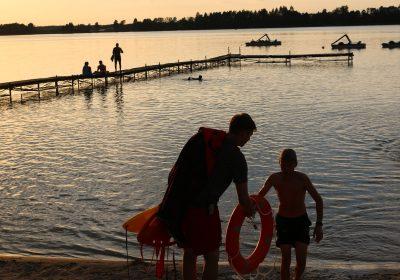 ratownik z kołem ratunkowym idzie z chłopcem nad jezioro