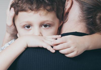 smutne dziecko przytulane przez mamę