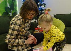Mała dziewczynka otwiera świąteczny prezent