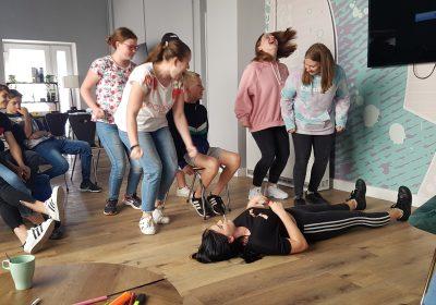 Grupa młodzieży bawi się na rozwojowych warsztatach